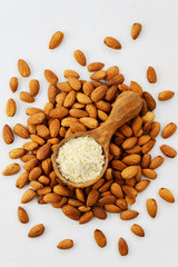 Almond flour in a wooden spoon on a background of almonds. Vertical orientation, top view. Healthy food, gluten free.