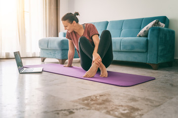 Tuinposter Ontspanning Attractive young woman doing yoga stretching yoga online at home. Self-isolation is beneficial, entertainment and education on the Internet. Healthy lifestyle concept