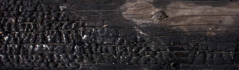 Black background. Burnt wooden Board texture. Burned scratched hardwood surface. Smoking wood plank background. Burned wooden grunge texture Space for text.