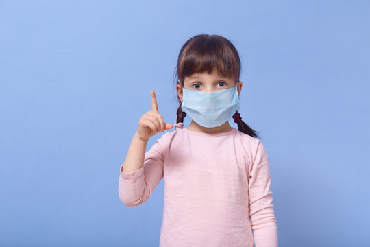 Indoor shot of little girl with wide opened eyes, wearing casual rose shirt and protective mask, pointing her index finger up, sign of attention. Protection against coronavirus, covid 19 concept.