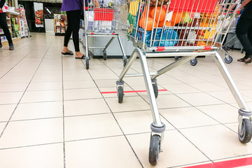 Social distancing being practiced at supermarket payment counter, with 1 meter gap between people in queue. Fototapete