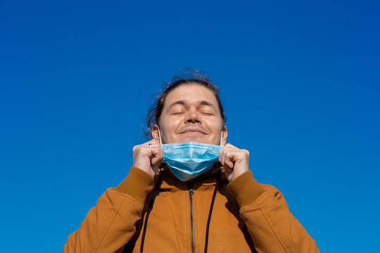 Close up portrait of a satisfied man with eyes closed taking off his medical mask and sniff fresh clean air on outdoor during a coronovirus quarantine pandemic.