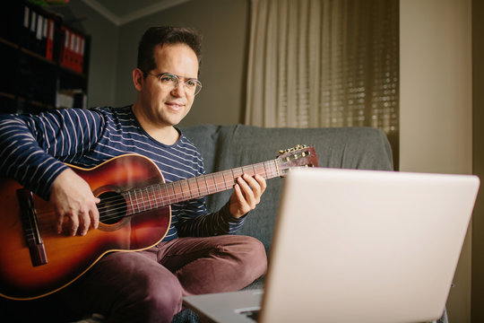 Boy taking an online course to learn how to play the classical Spanish flamenco guitar. He is sitting on the sofa at home, playing the guitar in front of the laptop while listening to the lessons.