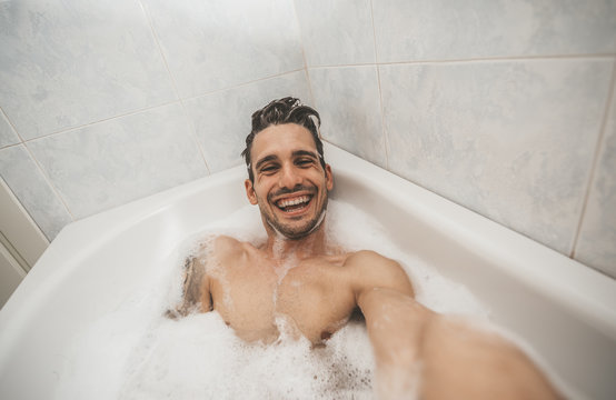 Happy handsome man take a selfie inside bathtub in the bathroom of the hotel on holiday.