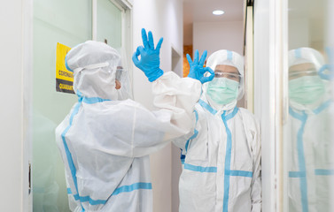doctor and nurse in personal protective equipments are greeting each other by touching elbow in the hospital. covid-19, coronavirus, social distancing, isolation, quarantine, medical concept