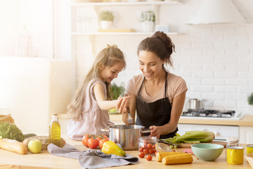 Mother and daughter preparing tasty food at kitchen.