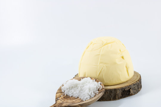 Motte de beurre salé baratté au sel de Guérande. sur un plateau en bois et une cuillère en bois de gros sel de Guérande photo studio sur fond blanc
