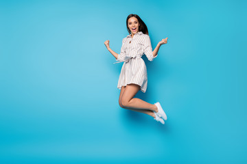 Full length profile photo of funny lady jump high rejoicing celebrate summer weekend vacation beginning wear spring striped mini dress footwear isolated blue color background Wall mural