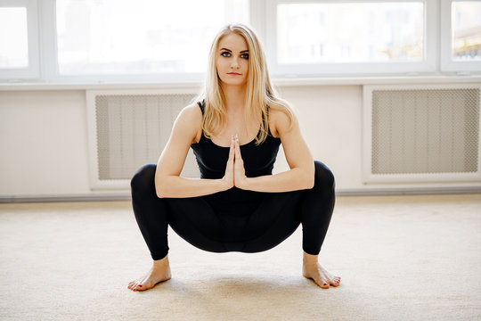 Sporty young woman in black sportswear sitting in squat, Garland Pose, Malasana with hands in Namaste. Front view. Fitness and stretching at home.