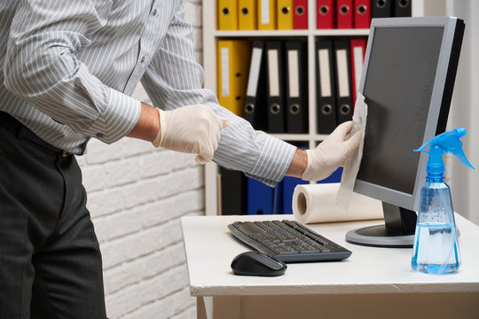 concept of cleaning or disinfecting the office - a businessman cleans the workplace, computer, desk, uses a spray gun and paper napkins. Cleaning surfaces from microbes, viruses and dirt.