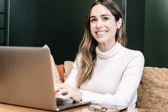 Smiling woman working with a laptop sitting on a couch and looking ahead