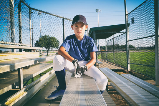 Male child baseball player sitting on bleachers