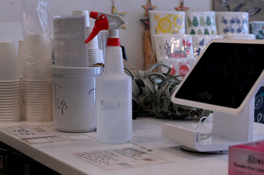A spray bottle of bleach is seen next to a tip jar and register  at Each Peach Market on the first day of new coronavirus protocols in Washington