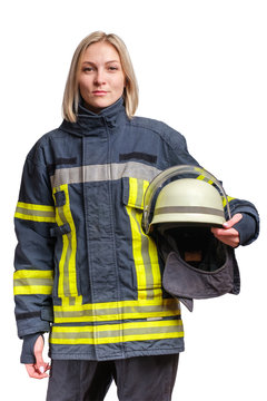 young caucasian woman firefighter in fireproof uniform stands and looks at the camera with helmet in her hands.