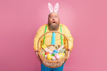 Portrait of his he nice amazed impressed funky glad bearded guy holding in hands giving you festal Easter craft basket bakery snack isolated over pink pastel color background