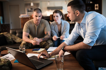 Financial advisor with laptop meeting with military couple