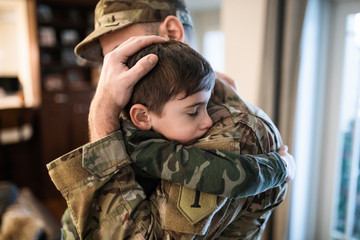 Soldier father holding son tenderly
