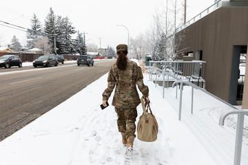 Female soldier in camouflage with duffel bag walking on snowy sidewalk