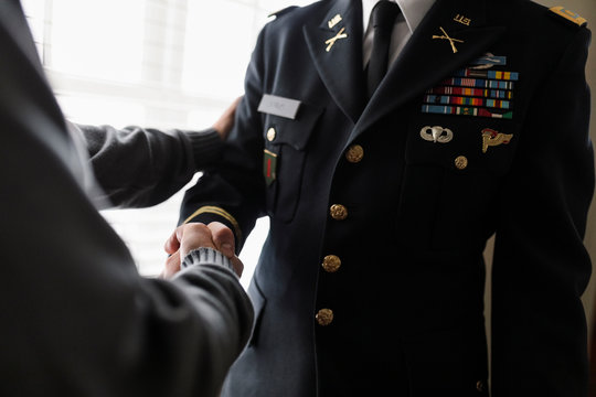 Close up father shaking hands with son in military dress uniform