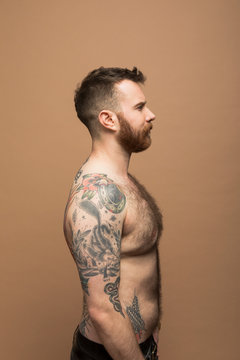 Profile portrait of transgender man with arm tattoos