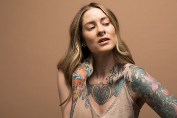 Portrait confident woman with tattooed arms and chest