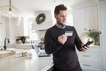 Man online shopping for Christmas with credit card on digital devices
