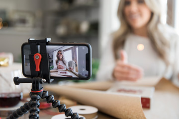 Woman vlogging on wrapping Christmas gifts