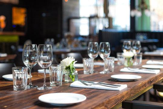 Glasses, flowers, fork, knife served for dinner in restaurant with cozy interior, retro film filter effect