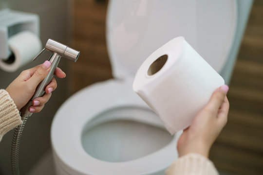 Woman make a choice, bidet shower or toilet paper.