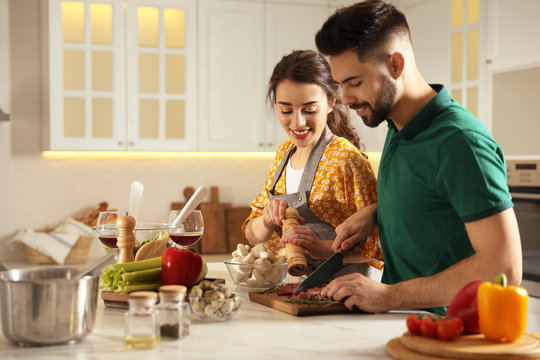 Lovely young couple cooking meat together in kitchen