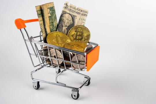 Bitcoins, euro, dollars and other currencies filling up shopping trolley, isolated on white background. To illustrate the financial and economic fluctuations and challenges during covid 19 crisis.