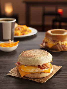 sandwich with egg and bacon, cheese for breakfast composition on a table with kartoka fries and bagels