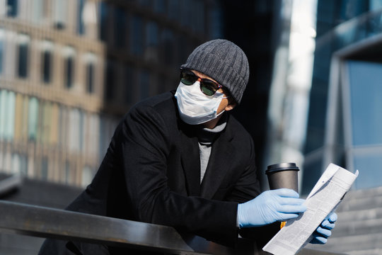 Young man at street with takeaway coffee and newspaper, wears protective medical mask and gloves, prevents spreading coronavirus, looks pensively aside, poses outdoor. Covid-19 pandemic, quarantine