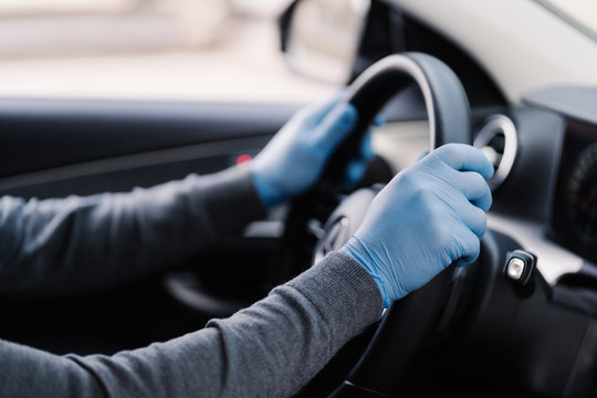 Health care in transport concept. Unrecognizable driver wears rubber protective gloves protects from coronavirus drives car during epidemic. Covid-19 protection concept. Disease, infection, quarantine