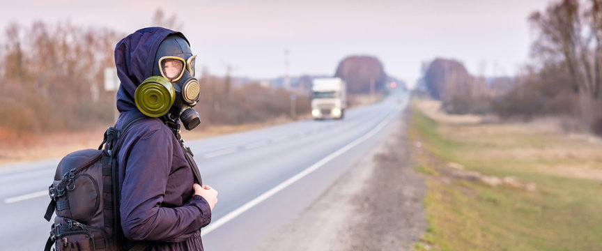A girl in a black gas mask stands on the edge of a suburban highway. Banner. The girl is trying to stop passing cars in order to leave the city in which the epidemic of coronavirus.