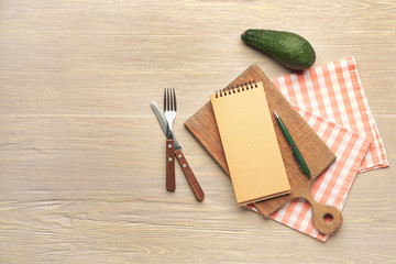 Notebook with board and cutlery on table