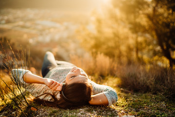 Obraz Carefree happy woman lying on green grass meadow on top of mountain enjoying sun on her face.Enjoying nature sunset.Freedom.Relaxing in mountains at sunrise.Sunshine.Daydreaming.Listening to music - fototapety do salonu