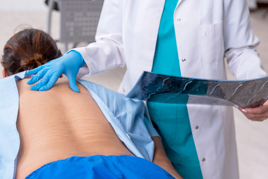 Young back injured man visiting female doctor chiropractor