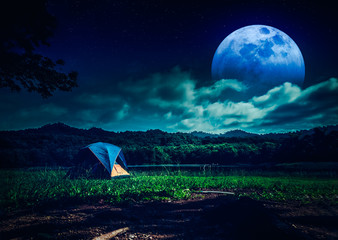 Wall Mural - Great view of camping tent near lake at night with many stars and full moon. The concept of travel, tourism, camping.