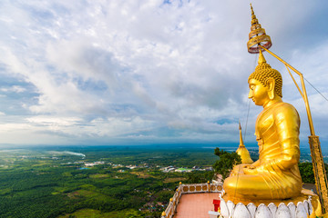Wall Mural - Golden statue on mountain sunruse with fog
