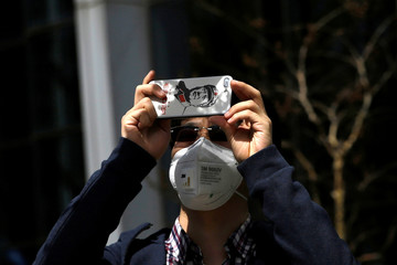 A man wearing a face mask uses his smartphone with an image of late Chinese chairman Mao Zedong on the phone case in Beijing