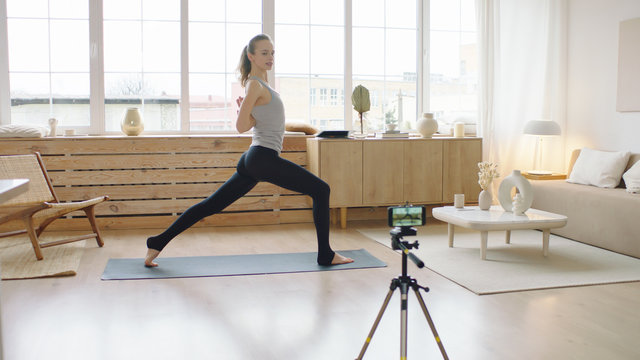 Attractive Caucasian recording making live stream or vlog about doing yoga at home. Stay home, quarantine workout