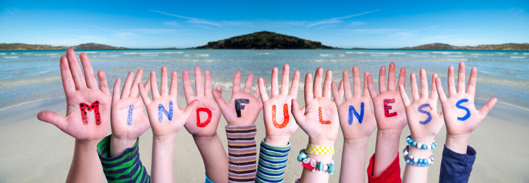 Children Hands Building Colorful English Word Mindfulness. Ocean And Beach As Background
