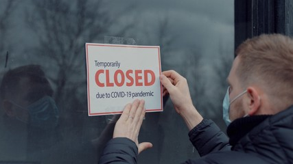 Caucasian male wearing medical mask puts a Temporary closed due COVID-19 pandemic sign on a window. Coronavirus pandemic, small business shutdown Fototapete