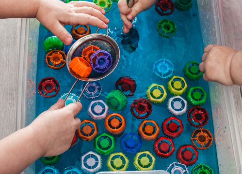 Children take out colored covers from the water. The development of children's motor skills using a sensory box. Development of children at home during a pandemic and quarantine