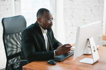 Typing text. African-american entrepreneur, businessman working concentrated in office. Looks serios and busy, wearing classic suit, jacket. Concept of work, finance, business, success, leadership.