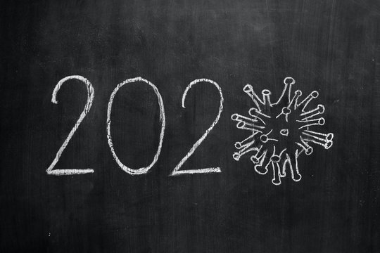 White chalk inscription 2020 year, image of virus SARS-CoV-2, 2019-nCoV, covid-19, acute viral respiratory infection that leads to pneumonia, on blackboard background. World coronavirus pandemic.