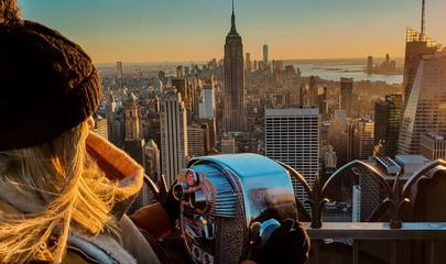 Frau steht vor Fernglas und blickt auf die Skyline von New York City Manhattan