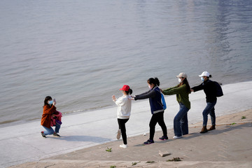 People wearing face masks pose for pictures by the Yangtze river in Wuhan