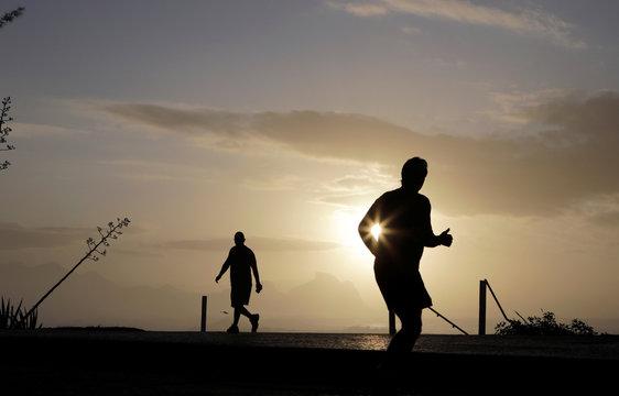 A man runs during a sunset at the Recreio dos Bandeirantes beach, amid the coronavirus disease (COVID-19) outbreak, in Rio de Janeiro
